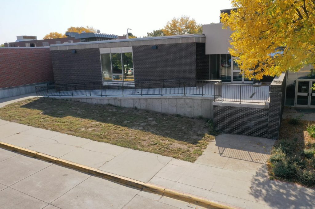 Grey Brick Building with Concrete Ramp and Metal Handrail